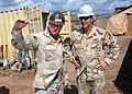 US Navy 061209-N-1328C-386 Commander, U.S. Naval Facilities Engineering Command Rear Adm. Richard E. Cellon speaks with Construction Electrician 1st Class Damien Brandlen, leading petty officer for the Tadjoura Primary school p.jpg