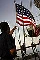 US Navy 071003-N-4774B-017 Quartermaster 2nd Class Jesus Aguilar lowers the national ensign at sunset aboard amphibious assault ship USS Tarawa (LHA 1).jpg