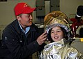 US Navy 071006-N-7981E-131 Aviation Boatswain's Mate (Handling) 3rd Class Woo Choe helps a young girl into a fire suit at a shipboard fire fighting display in the hangar bay of Nimitz-class aircraft carrier USS Abraham Lincoln.jpg