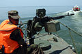 US Navy 090327-N-5242D-135 Uganda Peoples' Defense Force Pvt. Joriam Taremwa mans a machine gun at the bow of a Ugandan patrol boat in Africa's Lake Victoria where an Ilyushin 76 crashed March 9.jpg
