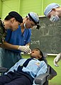 US Navy 090624-N-1722M-444 U.S. Navy dentist Lt. Brant Cullen, center, examines a student at Seberan Tayor Primary School.jpg