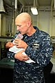 US Navy 100130-N-8936G-028 Rear Adm. David Thomas Jr., commander of Carrier Strike Group 2, feeds a Haitian infant in the medical department of the amphibious assault ship USS Nassau (LHA 4).jpg