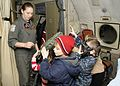 US Navy 110330-N-ZK021-009 Naval Air Crewman 2nd Class Jennifer Brawning explains functions of in-flight survival gear to children.jpg