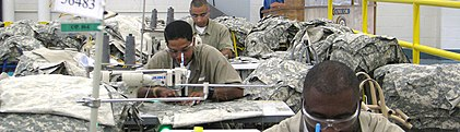 Prisoners sit at sewing machines, sewing military uniforms