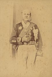 Photograph of an older man with long sideburns standing in a heavily embroidered cutaway jacket adorned with various medals and wearing a sash of office