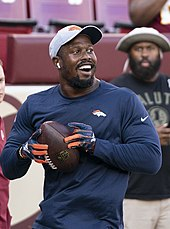 Von Miller wearing a cap and AirPods smiles while holding a football. He is also wearing gloves and looks like he might soon throw the ball.