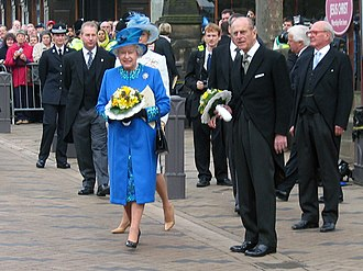 Royal Maundy - Queen Elizabeth II (centre, in blue) and Prince Philip hold nosegays as they leave Wakefield Cathedral after the 2005 Royal Maundy.
