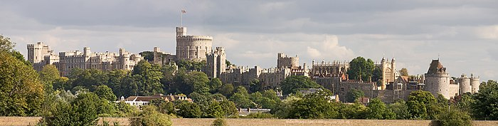 A photograph of a white-grey stone castle, running left to right; trees are in the foreground, with a large white tower the most prominent part of the castle in the middle of the shot.