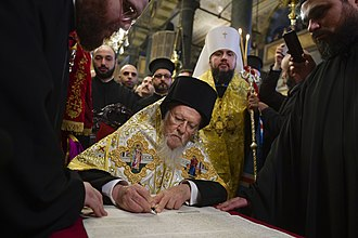 Orthodox Church of Ukraine - Patriarch Bartholomew signing the tomos. Epiphanius I of Ukraine (wearing a white klobuk) stands behind him.