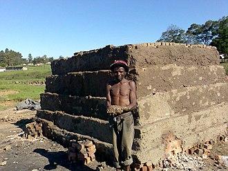 Brick clamp - Xhosa brick maker at a scove kiln near Ngcobo, South Africa