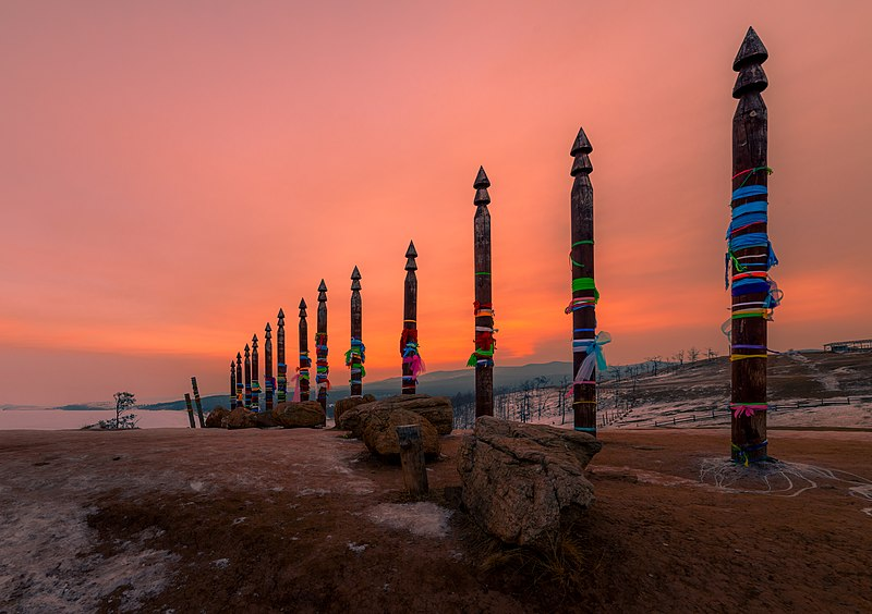 Carved pillars with colored ribbon (thick) on them in an orange sunset. Item of religious significance in Russia.