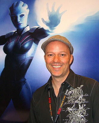 Mass Effect - Writer Mac Walters in front of a Mass Effect poster at the Dark Horse Comics booth at the 2011 New York Comic Con.