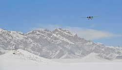 An aircraft flies past the Spin Ghar mountains on approach for a routine supply drop in Shah Joy district