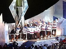 A group of men wearing white hockey jerseys surround a large torch. They light the torch and raise their arms in celebration.