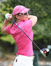 A blonde-haired woman in a pink shirt and hat with white pants and glove and a driver in her hand in the position at the end of a golf swing