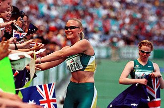Athletics at the 2000 Summer Paralympics - Australian track athletes Katrina Webb (left) and Alison Quinn (right) celebrate with their Australian fans in the crowd over their medal wins in the 100 m T38 at the 2000 Sydney Paralympic Games, Day 07. Quinn won gold and Webb won silver in this event.
