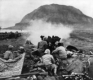 U.S. 37 mm gun fires against the Japanese cave positions