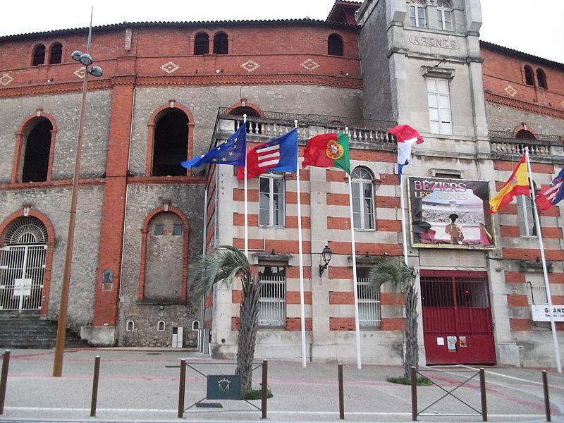 On peut voir plusieurs drapeaux à l'entrée des Arènes de la ville de Béziers, France. De gauche à droite, il y a le drapeau de l'Union européenne, le drapeau de la ville de Béziers, du Portugal, de la France, de l'Espagne et de nouveau celui de Béziers.