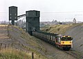 A Class 58 locomotive loads a merry-go-round train under the rapid loader at Ellistown, Leicestershire, with coal from the Coalfield Farm opencast site, Nigel Tout, October 1986.jpg