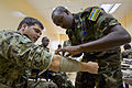 A Sudanese service member, right, applies a bandage to U.S. Navy Petty Officer 3rd Class Douglas Barton's arm during exercise Cutlass Express 2013 at the Port of Djibouti in Djibouti Nov. 13, 2013 131113-F-NJ596-036.jpg