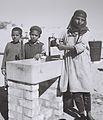 A YEMENITE WOMAN AND CHILDREN AT THE COMMUNAL WATER FOUNTAIN IN THE EZRA UBITZARON QUARTER IN RISHON LEZION. משפחת עולים מתימן בברזייה המשותפת בשכונה D842-005.jpg