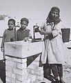 A YEMENITE WOMAN AND CHILDREN AT THE COMMUNAL WATER FOUNTAIN IN THE EZRA UBITZARON QUARTER IN RISHON LEZION. משפחת עולים מתימן בברזייה המשותפת בשכונה D842-005.jpg