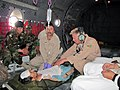 Afghan National Army medic, Ghulam Sakhi and Master Sergeant Kramer, Combined Power Transition Force, work to make a patient more comfortable on a C-27 Spartan during a mission from Mazar-e-Sharif .jpg