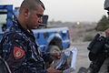 An Iraqi policeman with the local emergency services unit inspects antiterrorism flyers before handing them out at a traffic control point in Kirkuk province, Iraq, Aug 110801-A-YF193-023.jpg