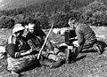 Båndfletting. En kvinne sitter og fletter bånd, to menn ved siden av henne. Lyngen, Troms 1947 - Norsk folkemuseum - NF.13712-014.jpg