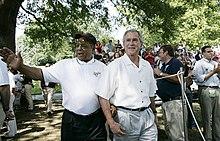 Fotografie a lui Mays și a președintelui George W. Bush purtând tricouri albe care treceau pe lângă o mulțime de oameni;  amândoi zâmbesc și Mays flutură
