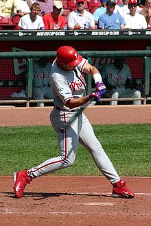 A man in a Philadelphia Phillies' uniform swinging a baseball bat