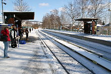 A snow-covered train station with a double track line. There are people waiting under the shelter on the left platform, while the right platform and shelter are empty.