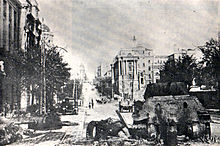 Photograph of a destroyed tank in a street