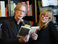Legs McNeil holds a book with Gillian McCain standing next to him