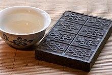 Une tasse remplie d'eau; à côté d'elle, une brique de thé.