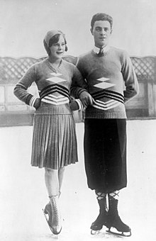 A woman and a man in figure skating blades stand on an outdoor ice rink posing for a shot. On the left, the woman has both hands in her waist, while the man has his right arm around her left arm.