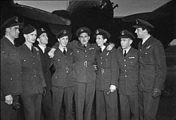 Portrait of a group of eight men in formal military uniform. All are wearing caps, and have their arms around each other. A large aircraft is in the background.