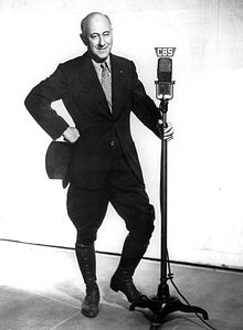Full body photograph of DeMille wearing a blakc suit, holding a top hat in one hand and the CBS radio microphone in the other