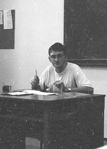 Cezary Geroń on a badly damaged black and white photograph, shown seated behind a teachers' desk.