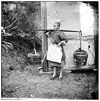 Night soil - A woman carrying buckets of night-soil, photographed in 1871.