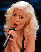 A picture of a blonde haired woman, singing while looking straight to the camera