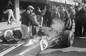 Colin Chapman - Chapman protects driver Jim Clark as mechanics work on his Lotus 33, a development of the monocoque Lotus 25 model, during practice for the 1966 Dutch Grand Prix