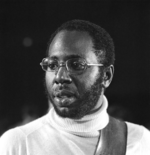 Black and white picture of a man with a beard wearing a turtleneck and glasses.