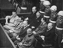 Photo noir et blanc prise en 1946, au procès de Nuremberg. Dans le box des accusés sont assis huit hommes, sur deux rangées de quatre. Au premier rang (de haut en bas): Hermann Göring, Rudolf Heß, Joachim von Ribbentrop et Wilhelm Keitel en uniforme. Au deuxième rang (de haut en bas): Karl Dönitz, Erich Raeder, Baldur von Schirach et Fritz Sauckel. Derrière eux (en haut, à droite), se tiennent quatre membres de la police militaire, debout, les mains derrière leur dos.