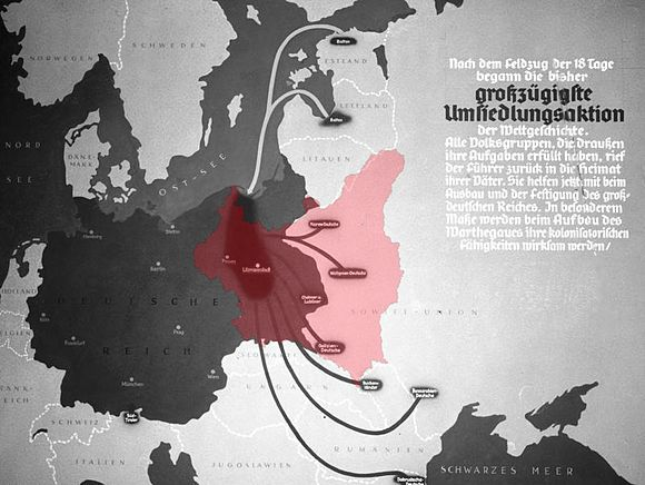 "The Third Reich in 1940 (dark grey) after the conquest of Poland together with the USSR, showing pockets of German colonists resettled into the annexed territories of Poland from the Soviet ""sphere of influence"" during the ""Heim ins Reich"" action. - The Nazi propaganda poster, superimposed with the red outline of Poland missing entirely from the original German print. Die 'grosszugigste Umsiedlungsaktion' with Poland superimposed, 1939.jpg"