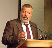 A man with a full beard, Dmitry Muratov, speaking at a podium