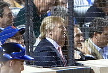 Trump at a baseball game in July 2009. He is wearing a baseball cap and sitting amid a large crowd, behind a protective net.