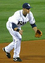 "A man in a white and blue baseball uniform with the letters ""TB"" on his cap kneels, preparing to field a ground ball."