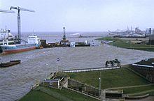 Морская дамба, где со стороны моря уровень воды явно на много метров выше уровня земли со стороны суши.