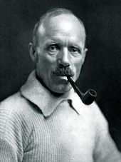 Head and upper body of a man, balding, smoking a pipe. He is wearing a heavy jersey.
